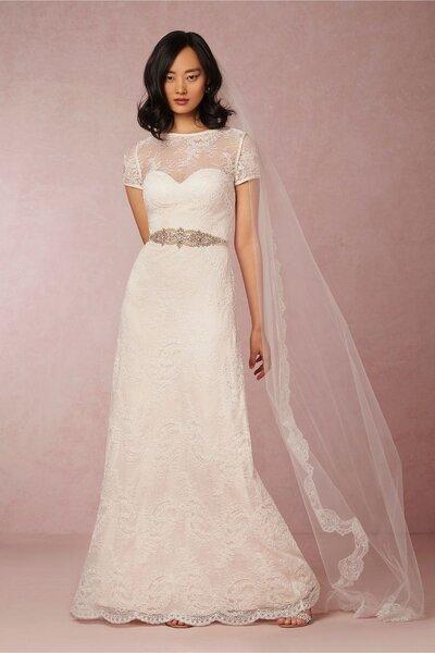 Vestido de novia en color blanco roto con escote ilusión cerrado, mangas cortas y cinturón cubierto con pedrería - BHLDN