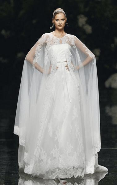 Vestido de novia en color blanco con capa transparente superpuesta y escote strapless