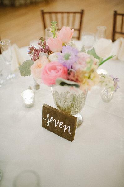 Centro de mesa com flores belíssimas e número com caligrafia trendy.