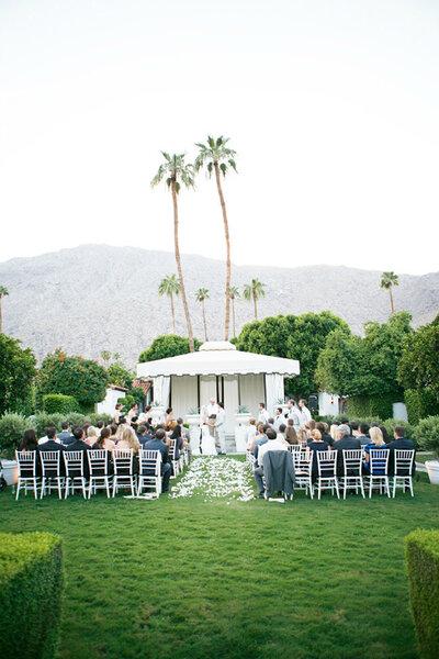 Outdoor, unter einem weißen Zelt und tropisch inspiriertem Hintergrund. Foto: Lane Dittoe