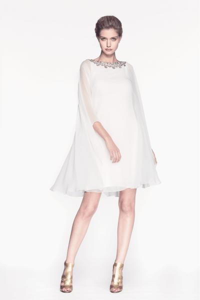 vestido de fiesta corto en color blanco con escote discreto llenos de pedrería y capa superpuesta
