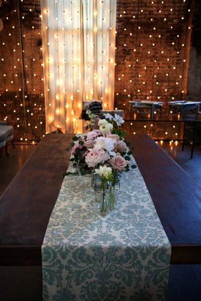 Estampa de damasco na mesa e luzes atrás para um casamento muito chic. Foto: Zaugh Photography