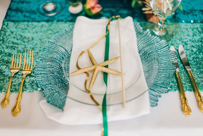 Decoración marina para el banquete en dorado y azul verdoso.