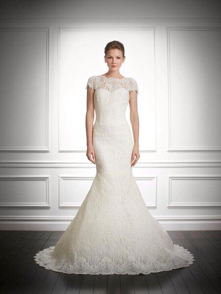 Vestido de novia con silueta ceñida, mangas largas, escote ilusión y detalles en relieve