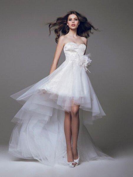 Vestido de novia corto con cauda larga y escote corazón; detalles de flores en el costado y falda confeccionada en tul