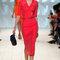 Vestido rojo con escote en v, mangas tres cuartos y cinturón ajustado.