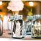 Hochzeitsdeko mit Gläsern und Vasen. Foto: Jessamyn Harris