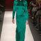 Vestido de fiesta largo en color verde con acabado en satén, estilo minimalista, cauda y mangas largas