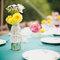 Decoración de mesa de boda con mantel turquesa y botellas de cristal