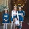 Damas e pajem vestidos em tom de azul com faixa estampada.