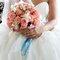 17. Una foto a detalle del ramo de novia con un lazo en color azul como adorno