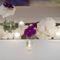Arreglo de mesa largo con flores blancas, moradas y velas para boda