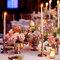 Arreglos de mesa para bodas de noche en vasitos dorados con flores rosas y naranjas y velas de adorno