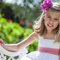 Vestido branco contrastando com faixa e flor rosa de Pikiliki.