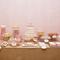 Decoración para mesa de postres estilo femenino en colores neutros como el rosa pastel y mantel en tono nude
