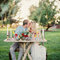 Un repas de mariage célébrer dans la forêt autour d'une table de pique nique.