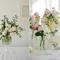 Arreglos de mesa para bodas elegantes con flores en colores blanco y rosa pálido y envases de cristal