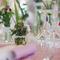 Arreglos de mesa para boda con flores coloridas en tonos rosa intenso en jarrones de cristal vintage