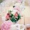 Mesa de banquete decorada con pequeños centros de flores y velas.