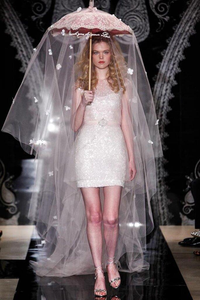 Vestido de novia corto con cuello ilusión, mangas cortas y detalle de pedrería en la cintura - Foto Reem Acra