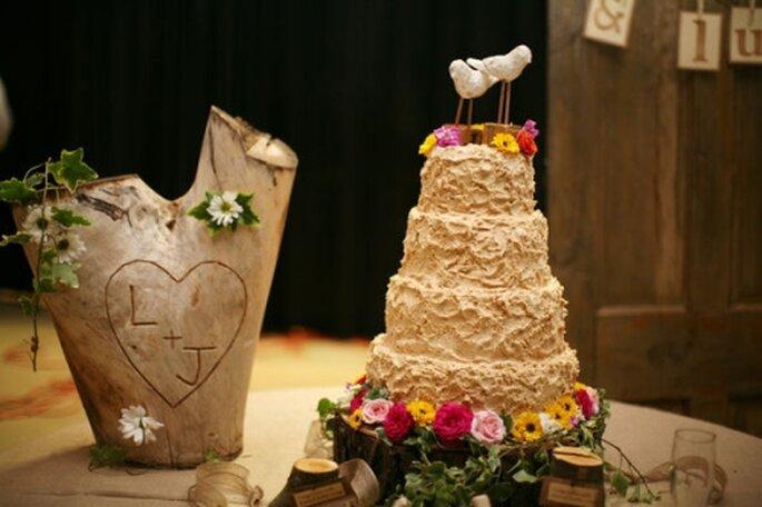 Pastel de boda color marfil, decorado con flores de colores y dos pájarillos