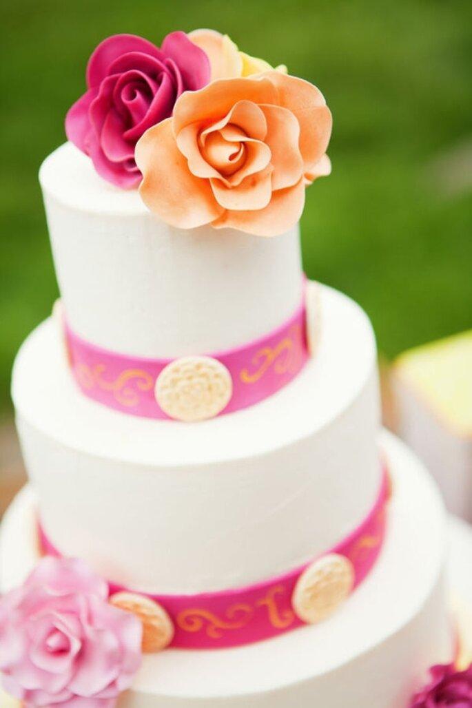 Pastel de boda blanco, decorado con cintilla rosa y flores naturales