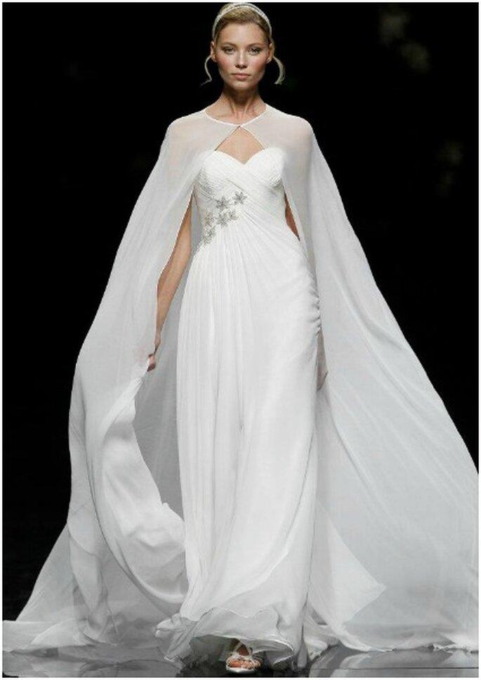 Vestido de novia con capa de gasa y detalles de cristales en la cintura. Foto: Pronovias