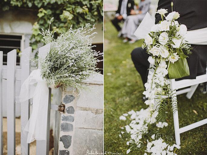 Sillas blancas decoradas con flores naturales para un aboda al aire libre. Foto: Roberto y María