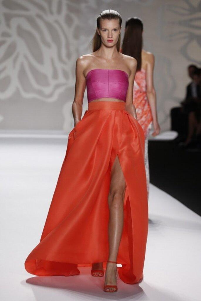 Falda larga con cauda y abertura al frente acompañada de un crop top en tono rosa intenso con escote strapless - Foto Monique Lhuillier