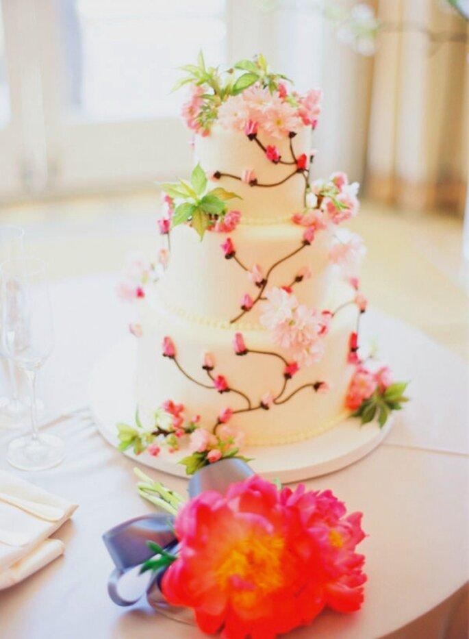 Pastel de boda blanco, adornado con flores de cerezo rosa