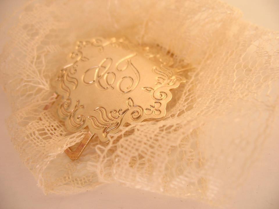 Medalha buquê com monograma dos noivos.
