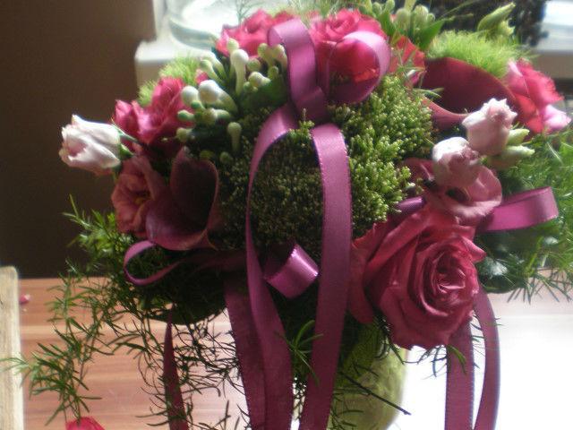 Beispiel: Blumenkranz mit pinken Blumen und Schleifen, Foto: Blumenstudio Marzahn.