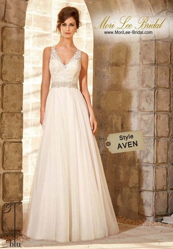 Dress Style AVEN Majestic Embroidered Bodice With Crystal Beaded Waistline Trim On Soft Net Gown Majestic embroidery lay atop ethereal Net on this romantic A-line wedding dress. Accented with a dramatic V-neck and a delicate illusion back. A beaded waistline gives the illusion of a belt at the waist. Finished with covered buttons. Colors Available: White/Silver, Ivory/Silver, Light Gold/Silver