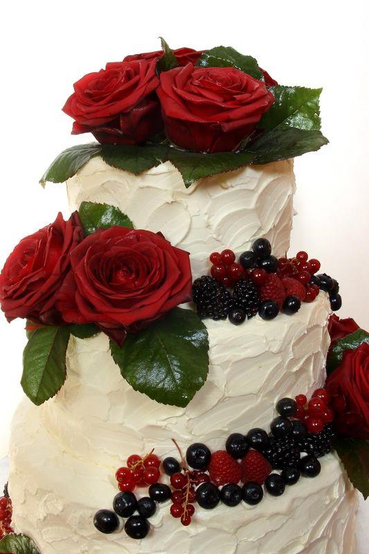 Dreistöckige Hochzeitstorte mit Buttercreme Struktur, frischen Rosen und Beerendekoration