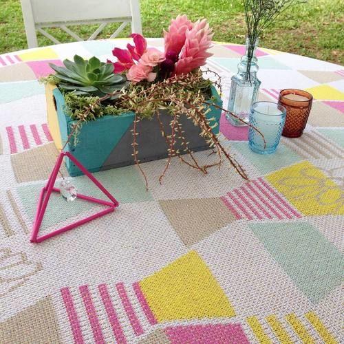 Na toalha de mesa nossa estampa exclusiva. A caixinha, figura geométrica e arranjo de flores são handmade