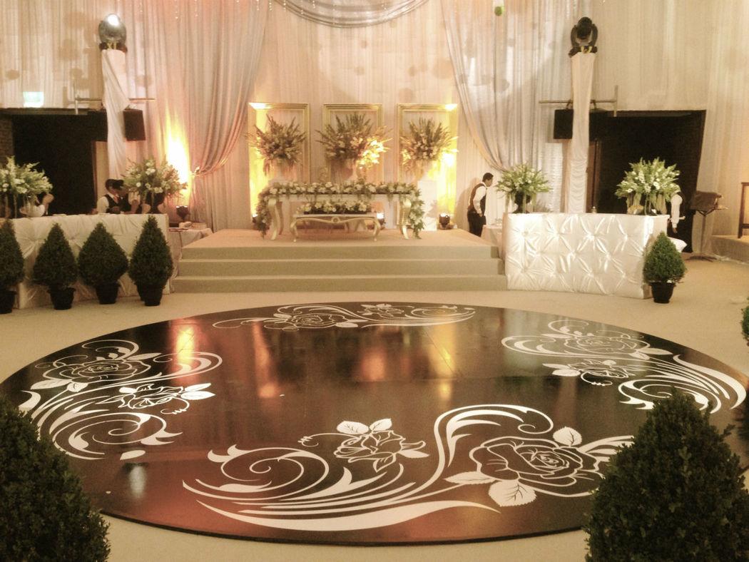 Pista de Baile en Vinil y diseño especial para los novios, barra de bebida al fondo en cada extremo y centrado la mesa de novios sobre una tarima