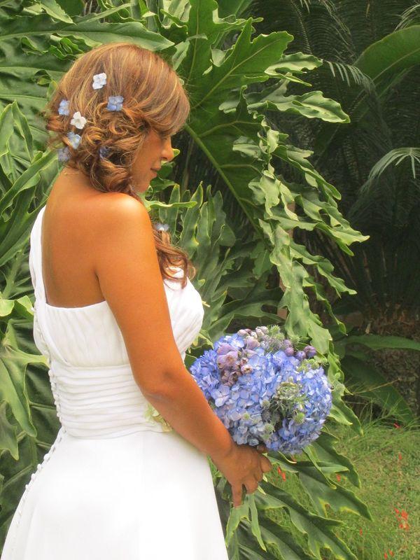 La novia luce unas pequeñas flores en cascada al tono de su ramo.