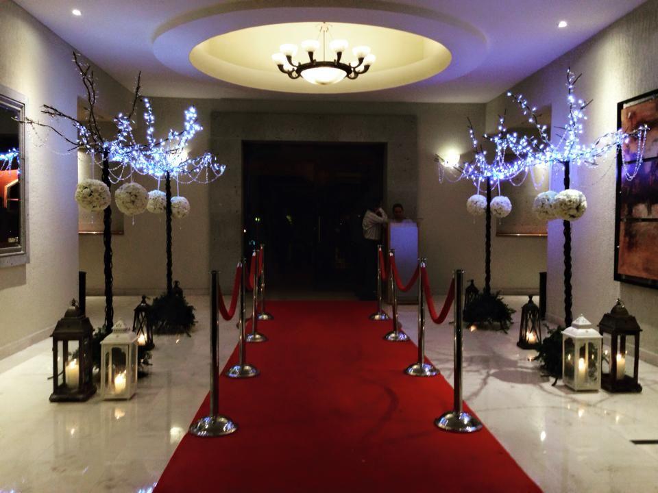 Camino de entrada en salón Casa Magna decorado con arboles de led, topiarios de rosas blancas y bellos faroles vintage.
