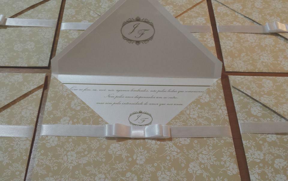 Convite com envelope clássico no tamanho 17x23cm, revestido em tecido e com aplicação de papel perolado com monograma na lapela.