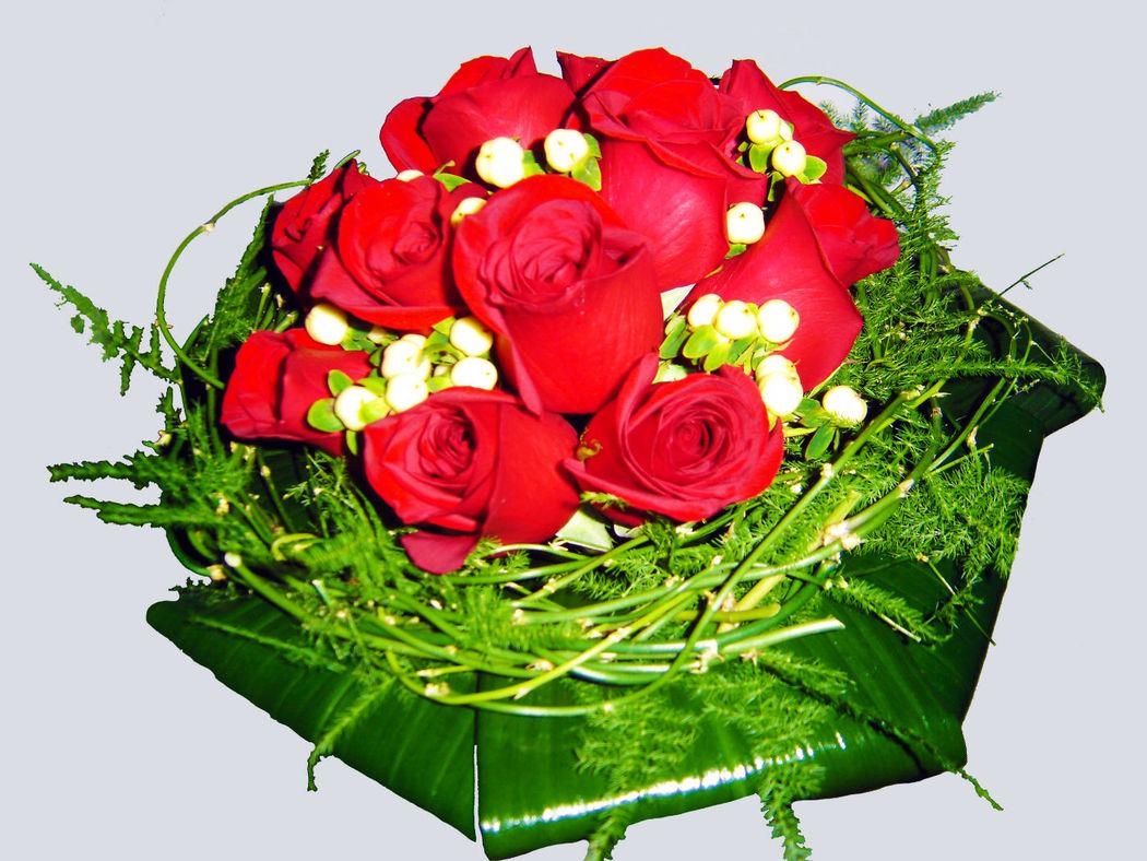 Ramo de novia tipo nido con rosas rojas y hojas de aspidistra.