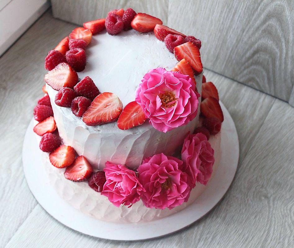 Романтичный двухъярусный торт с цветовым приливом от розового к серому, украшен кустовой розой и красными ягодами. Прекрасное украшение свадьбы в розовых тонах.