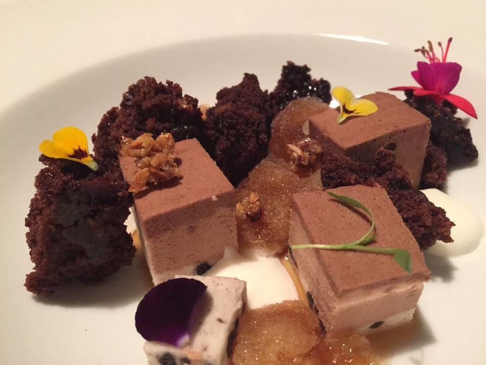 Mousse de tres chocolates, bizcocho de avellanas, granizado de café, flores.