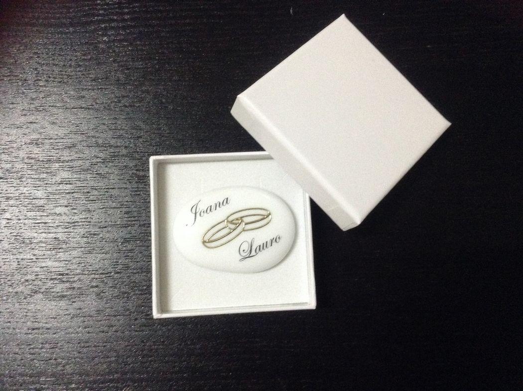 Pedra com nomes dos noivos e alianca dourada, em caixa branca