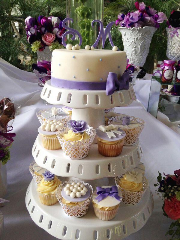 Pastel con iniciales de los novios y cupcakes