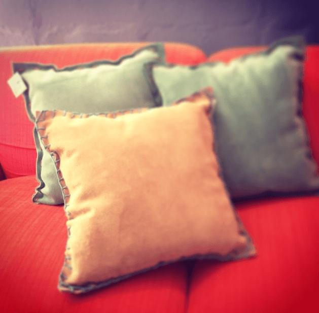 Almofadas de camurça com a costura em fio de couro colorido.  Medidas : 50cm x 50cm