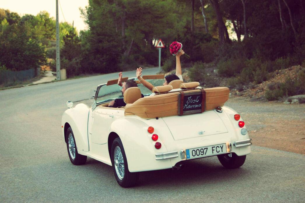 Los novios salen conduciendo el Albaycín Blanco después de la ceremonia, con la pizarra Just Married que colocamos en la parte trasera,