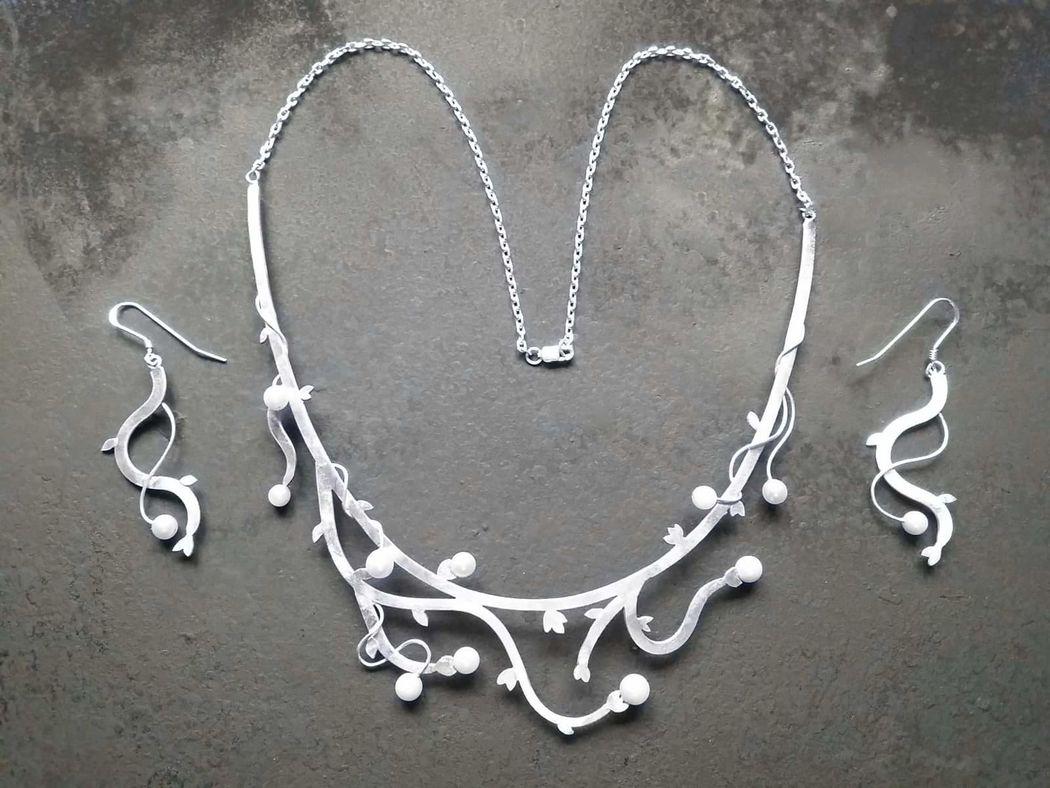 Conjunto de plata 950 representando una enredadera, con detalles de perlas en las puntas, los aros hacen juego para no quedarse atrás.