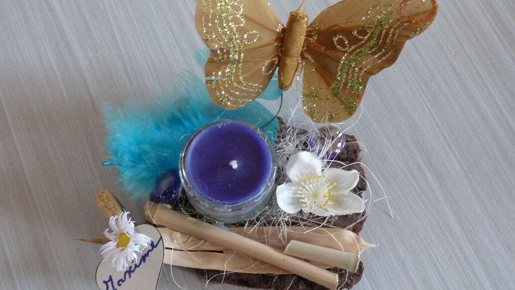 Souvenir d'invité en écorce et bambou, papillon,plume, bougie et fleur.
