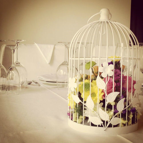 Centro de mesa de flores variadas dentro de una jaula decorativa