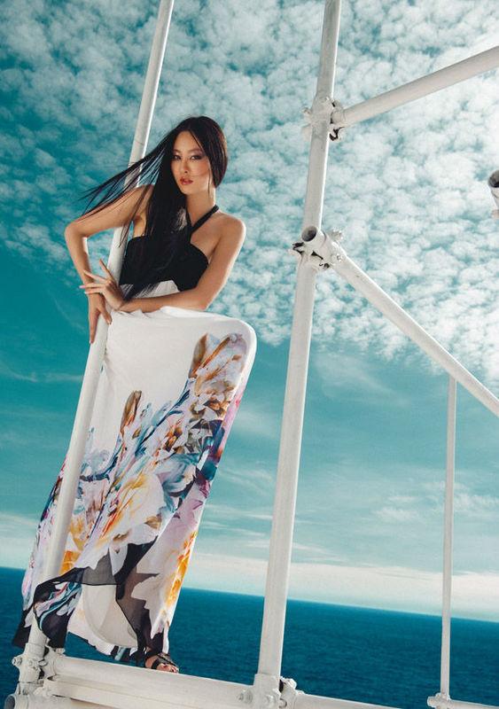 Una stampa floreale su fondo bianco per un abito con corpino in microrete drappeggiata. Sandali in raso nero della collezione Fabiana Ferri Shoes & Bags S/S 2014
